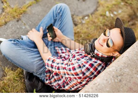 summer holidays, teenage and technology concept - teenager with headphones and smartphone outside