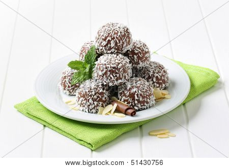 belgian pralines sprinkled with coconut, on a plate with linen