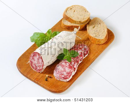 saucisson sec with bread served on a wooden cutting board