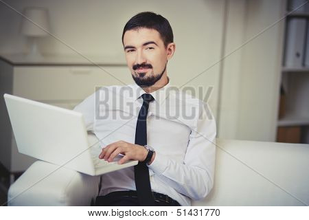Portrait of posh guy with laptop looking at camera