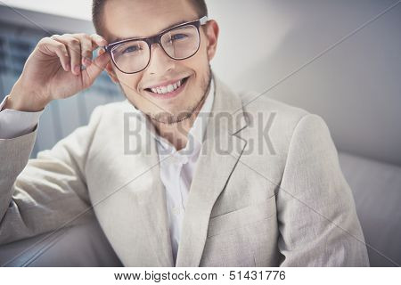 Portrait of posh guy in eyeglasses looking at camera