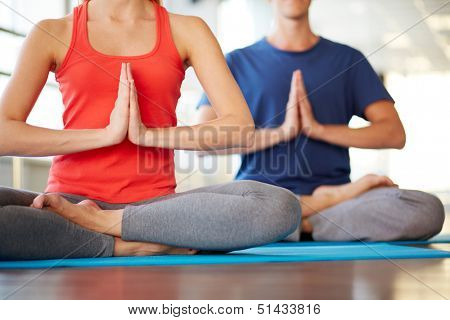 Lower part of young woman doing yoga exercise with guy on background