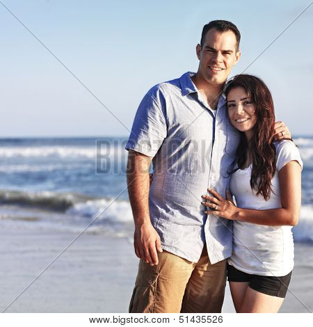 happy romantic couple by the ocean hugging