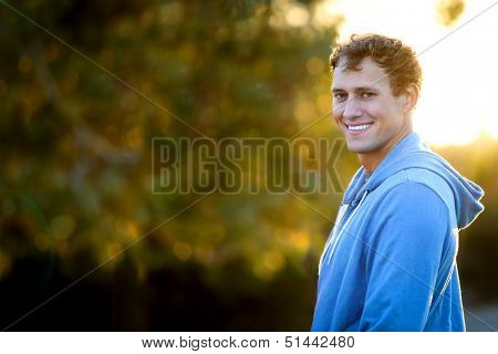 Young man standing outside in the sun