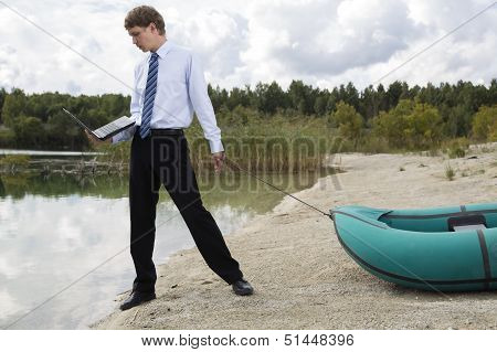 Dressed Man Plan Drags Boat At Lake
