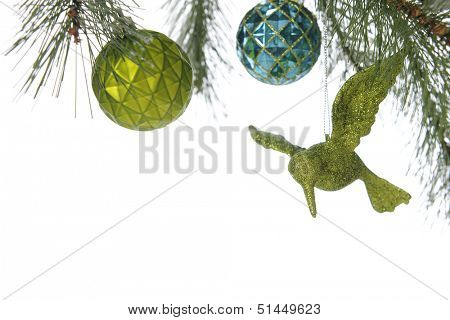 A top boarder under the boughs of a decorated Christmas tree, revealing a round green and blue bulb and a sparkly green humming bird ornament.  On a white background.