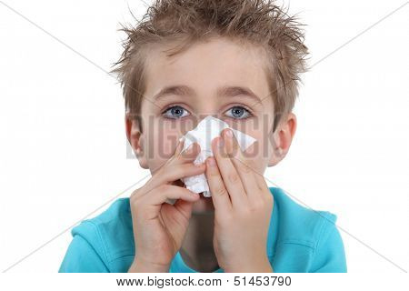Young boy blowing his nose