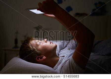 Boy Looking At Digital Tablet In Bed At Night