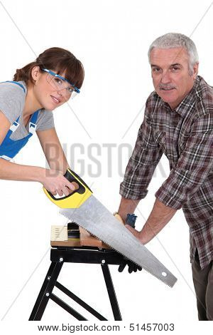 Father and daughter sawing plank of wood