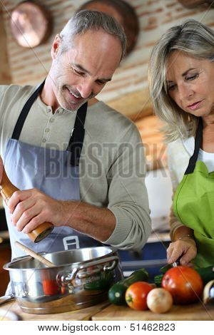 Senior couple in kitchen preparing dinner