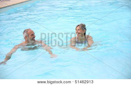 Active senior couple in resort pool