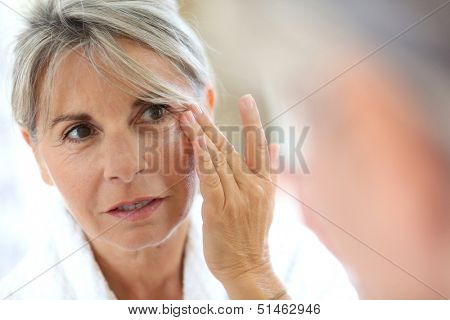 Senior woman applying anti-wrinkles cream