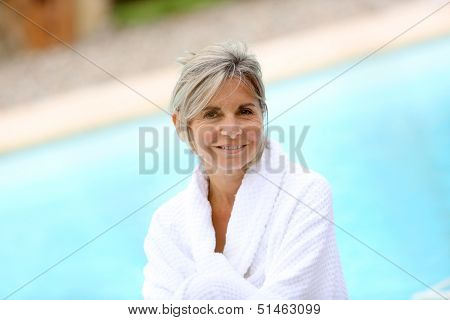 Portrait of smiling senior woman sitting by resort pool