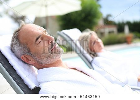 Senior man in spa hotel relaxing in long chair