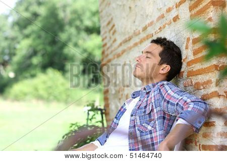 Man relaxing on bench during week-end in countryside