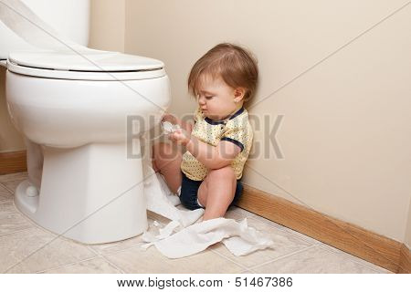 Toddler ripping up toilet paper