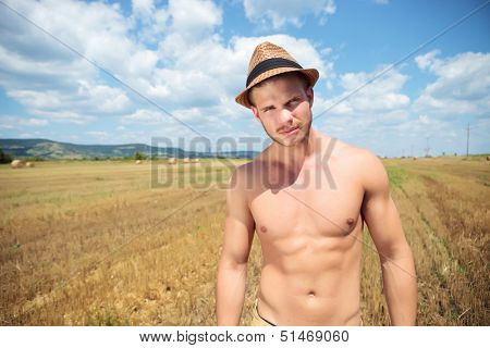 young topless man posing outdoor while wearing a trilby hat and looking into the camera