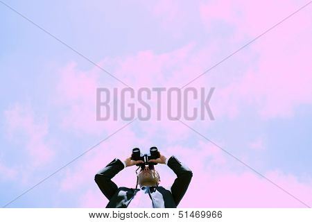 Businessman looking through binoculars, low angle view