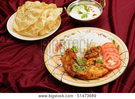 Kashmiri chicken in a serving bowl beside a plate of pappadums and a bowl of raita. The chicken is marinated with tomato and spice paste and the fried with ginger and garlic.