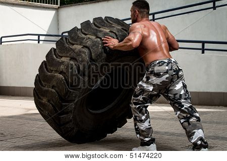 A Muscular Man Participating In A Cross Fit Workout By Doing A Tire Flip
