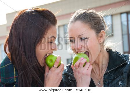 Happy Girls Eat Green Apples Outdoors