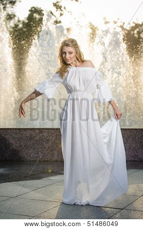 Attractive girl in white long dress sitting in front of a fountain in the summer hottest day