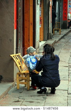 Chinese Woman Feeding Baby
