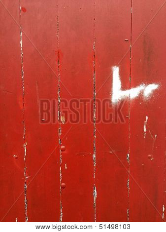 Closeup of red flaking paint on boards