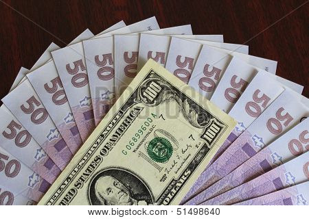 dollar and grivnas banknotes on dark background
