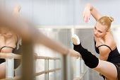 stock photo of ballet barre  - Ballerina stretches herself near barre and mirrors in the classroom - JPG