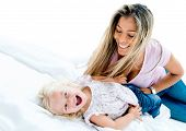 stock photo of tickling  - Beautiful portrait of a happy woman tickling a girl in bed - JPG