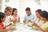 stock photo of 11 year old  - Multi Generation Indian Family Eating Meal At Home - JPG