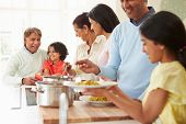 stock photo of 70-year-old  - Multi Generation Indian Family Cooking Meal At Home - JPG