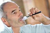 stock photo of substitutes  - Portrait of senior smoker with electronic cigarette - JPG