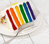 stock photo of sprinkling  - Slice of colourful rainbow layered birthday cake decorated with sprinkles - JPG