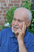image of senior men  - A Hispanic senior adult male is looking away in a pensive mood - JPG