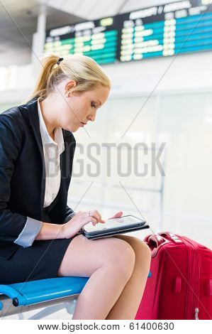 a business woman using her tablet computer at an airport. mobility and communication in business. roaming charges when abroad.