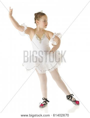 A young elementary ballerina poised to being her performance in her white dance costume.  On a white background.