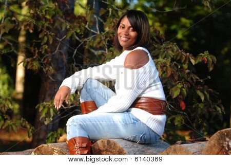African-american Woman Sitting On Log