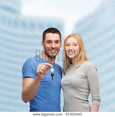 real estate, family and couple concept - smiling couple holding keys