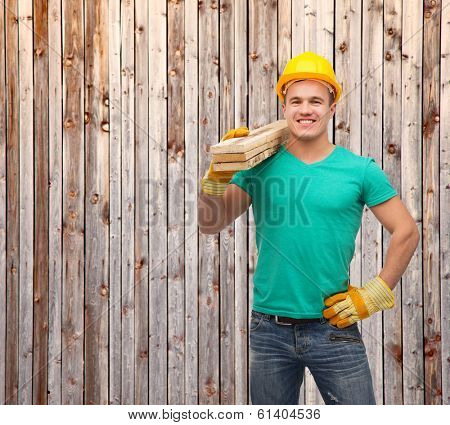 repair, construction and maintenance concept - smiling male manual worker in protective helmet carrying wooden boards