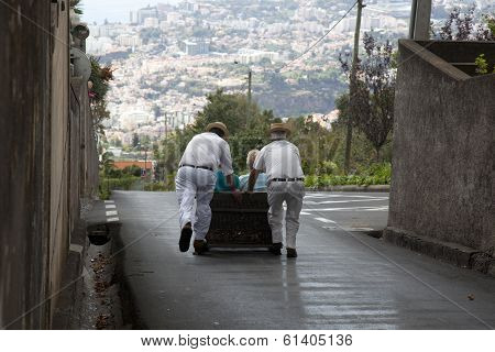 FUNCHAL, PORTUGAL- NOVEMBER 01: Toboggan riders starting dive with the sledge on
