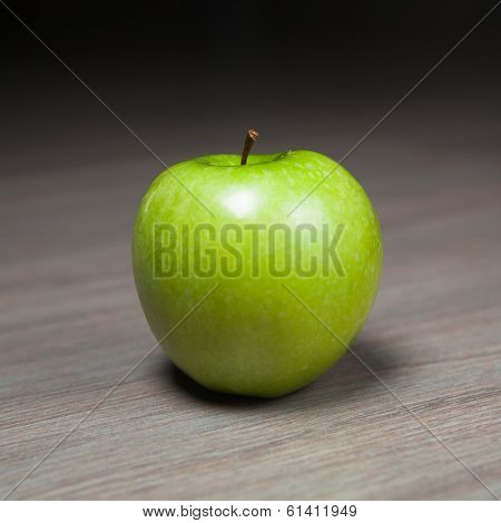 granny smith green apple against wooden background