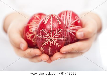 Child hands holding dyed traditional easter eggs with handmade patterns