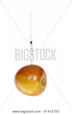 Apple with needle sticking out of it signifying our food supply being doped with artificial drugs, vitamins and steroids