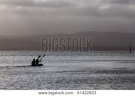 Two men paddle a canoe on a lake in Australia