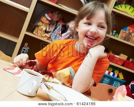 smiling laughing little girl eating breakfast at kindergarten