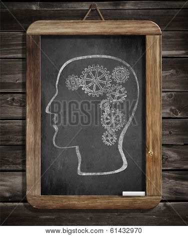 Human brain mechanism with cogs and gears drawn by chalk on blackboard