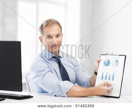 picture of handsome businessman showing graphs and charts