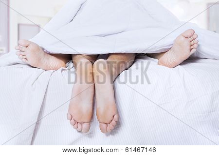 Pairs Of Feet In A Bed